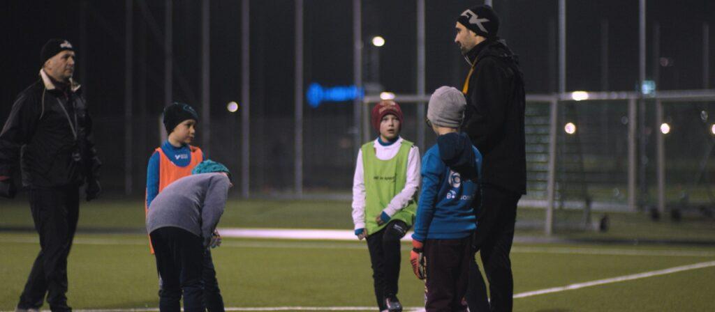 Två ledare och fyra barn på en fotbollsplan