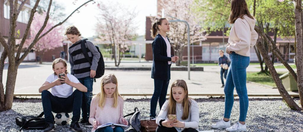 Elever som står och sitter på en skolgård